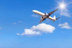 El aeroplano que se va volando adentro a la altitud altísima sobre el blanco se nubla con luz del sol Imagen de archivo libre de regalías