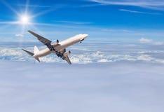 El aeroplano que se va volando adentro a la altitud altísima sobre el blanco se nubla con luz del sol Imagenes de archivo