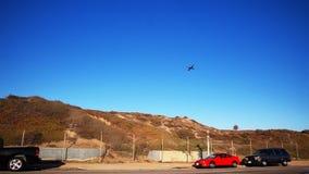 El aeroplano vuela sobre la colina y los coches parqueados metrajes