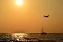 El aeroplano y el velero en fondo de la puesta del sol Imagen de archivo