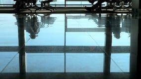 El aeropuerto, sala de espera, en el piso tejado es figuras reflejadas de la gente Las figuras oscuras de la gente se apresuran d almacen de metraje de vídeo