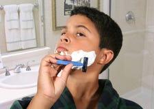 El afeitar joven del muchacho foto de archivo