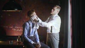 El afeitar tatuado de su cliente tatuado, peluquería de caballeros de los finales en el estilo de la mafia de los años 30, afeita metrajes