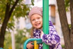 El aferrarse sonriente de la muchacha a la verja del metal del children& x27; s resbala en la yarda Fotos de archivo