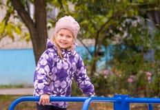El aferrarse sonriente de la niña al children& x27; s resbala en la yarda Fotografía de archivo