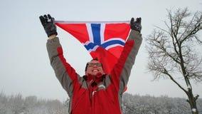 El aficionado deportivo feliz del hombre sostiene la bandera de Noruega que agita en el viento metrajes