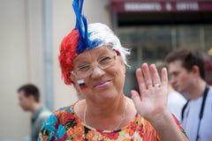 El aficionado deportivo ruso viejo de la mujer con la bandera rusa en su mano que da la bienvenida de la mejilla firma adentro Mo Foto de archivo