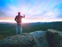 El aficionado toma las fotos con el teléfono en el pico de la roca Paisaje soñador, caída de Sun en horizonte Imagen de archivo