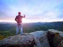 El aficionado toma las fotos con el teléfono en el pico de la roca Paisaje soñador, caída de Sun en horizonte Foto de archivo libre de regalías
