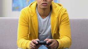 El aflojarse afroamericano del adolescente, jugando a los videojuegos en el sofá, forma de vida del ocio almacen de video