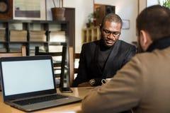 El africano multicultural y los hombres de negocios cauc?sicos negocian en un caf? Maqueta imágenes de archivo libres de regalías