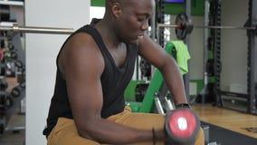 El afroamericano del hombre balancea su bíceps con una pesa de gimnasia en el gimnasio almacen de video