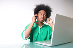 El afroamericano escucha la música con la computadora portátil Imagenes de archivo