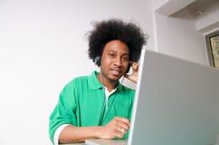 El afroamericano escucha la música con la computadora portátil Foto de archivo