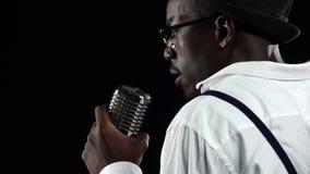 El afroamericano la oscuridad viene al micrófono que canta en un estudio de grabación Fondo negro Cámara lenta almacen de video