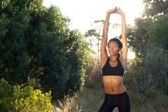 El afroamericano se divierte a la mujer con los brazos aumentados al aire libre Imagenes de archivo