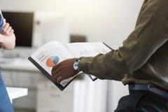 El afroamericano sirve las manos que llevan a cabo el documento en una oficina Imágenes de archivo libres de regalías