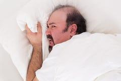 El agarrar insomne en su almohada en la desesperación foto de archivo