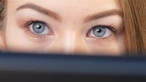 El agente de la muchacha supervisa el cambio del comercio en su ordenador en línea almacen de metraje de vídeo