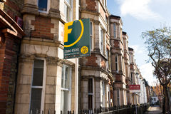 El agente de la propiedad inmobiliaria firma fuera de una fila de casas colgantes victorianas Foto de archivo