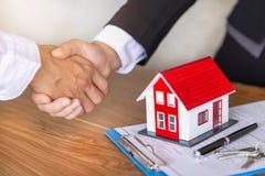 El agente de la propiedad inmobiliaria que sacude las manos con el cliente despu?s de firma de contrato, negocio firmando una cas imagen de archivo