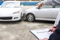 El agente de seguro examina la forma de demanda dañada del informe del coche y de la limadura fotos de archivo