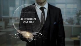 El agente de sexo masculino, jefe del inicio crypto de la moneda muestra el efectivo de Bitcoin de las palabras en su mano almacen de video