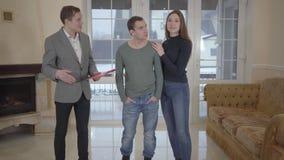 El agente inmobiliario acertado muestra a pareja de matrimonios linda confiada joven un nuevo hogar Hombre feliz y mujer que mira metrajes