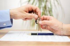 El agente inmobiliario da llaves de la casa a su cliente después de firmar c Imagen de archivo libre de regalías