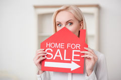 El agente inmobiliario femenino atractivo está vendiendo una casa Fotos de archivo libres de regalías