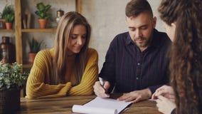 El agente inmobiliario femenino está leyendo la compra y el acuerdo de la venta a los pares jovenes, hombre está firmando el docu almacen de metraje de vídeo