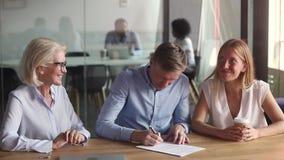 El agente inmobiliario hacer trato de las propiedades inmobiliarias con los pares felices firma el contrato almacen de metraje de vídeo