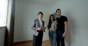 El agente inmobiliario profesional muestra la casa moderna a un par joven almacen de metraje de vídeo
