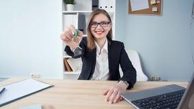 El agente inmobiliario sonriente de la mujer joven entrega las llaves a las nuevas propiedades inmobiliarias metrajes