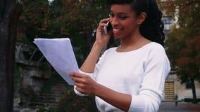 El agente inmobiliario tiene conversación con el cliente, el hablar bastante femenino en el teléfono almacen de metraje de vídeo