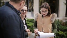 El agente inmobiliario y los pares jovenes están discutiendo los matices del arriendo o compran la venta de las propiedades inmob almacen de metraje de vídeo