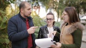 El agente inmobiliario y los pares jovenes están discutiendo los matices del arriendo o compran la venta de las propiedades inmob almacen de video