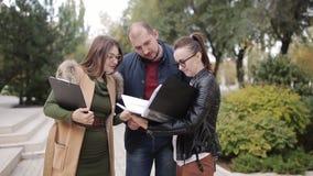 El agente inmobiliario y el progulyatsya joven de los pares el callejón y discuten el arriendo o la compra de un nuevo hogar metrajes