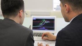 El agente mayor explica las cartas en la pantalla del ordenador portátil a su colega menor almacen de video