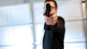 El agente secreto aumenta la pistola del arma de fuego en la cámara en la bahía ALT del hangar metrajes
