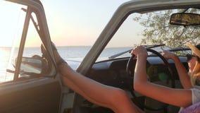 El agitar agradable de la muchacha viene conmigo detrás del auto de la rueda en la luz del sol, viaje feliz de la mujer joven al  almacen de video