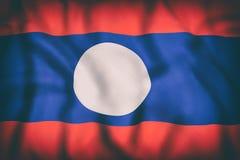 El agitar de la bandera de la república Democratic del ` s de Lao People Fotos de archivo libres de regalías