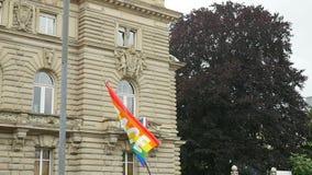 El agitar de la cámara lenta de la bandera del arco iris con las letras de la paz con el edificio en fondo almacen de metraje de vídeo