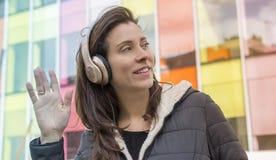 El agitar, muchacha en la calle que escucha la música con los auriculares encendido Fotografía de archivo