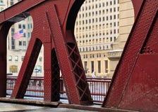 El agitar visto de la bandera americana con la arquitectura de un puente de Chicago en el lazo Imagen de archivo libre de regalías