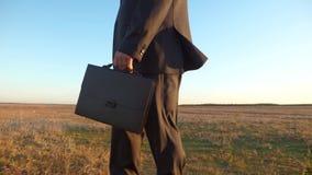El agrónomo, granjero va en su tierra y examina el campo contra un cielo azul hombre de negocios en traje serio con metrajes