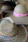 El agrupar de los sombreros de paja en la tabla Foto de archivo