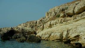 El agua azul del mar transparente lava la orilla de piedra Grecia almacen de video