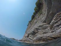 El agua azul del mar y de los coas rocosos Fotografía de archivo