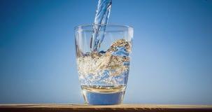 El agua azul está fluyendo en el vidrio que forma burbujas y salpica metrajes